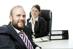 Kvinna för brunett för skäggaffärsman på skrivbordleendet royaltyfri foto