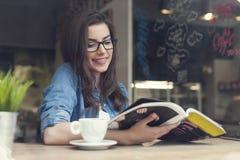 kvinna för cafetidskriftavläsning Arkivfoton