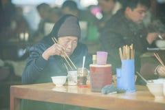 Kvinna för etnisk minoritet i restaurang på den gamla Dong Van marknaden Royaltyfria Bilder