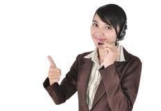 Kvinna för felanmälansmitt med hörlurar med mikrofon som visar upp tumen Arkivbild
