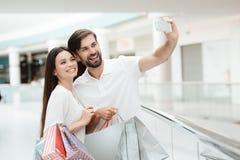 kvinna för galleriamanshopping Paret tar selfie på telefonen arkivfoto