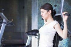 kvinna för idrottshallutbildningsvikt Att öva på drar ner viktmaskinen Kvinna som gör handtag-UPS som övar lyftande hantlar Cardi Arkivbild