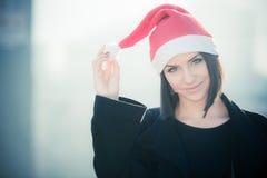 Kvinna för juljultomtenhatt som utomhus ler ståenden Le den lyckliga flickan som bär hennes jultomtenhatt med stads- bakgrund för royaltyfri bild