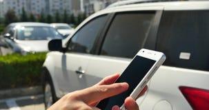 kvinna för 4k som A använder en smartphone i parkeringshus arkivfilmer