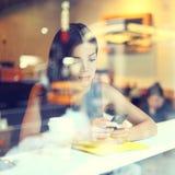 Kvinna för kaféstadslivsstil på telefonen som dricker kaffe fotografering för bildbyråer