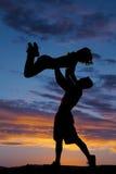 Kvinna för kast för konturparman upp solnedgång arkivfoto