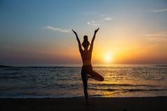 Kvinna för kondition för yogakonturmeditation på havet arkivbild