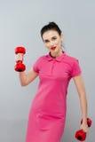 Kvinna för konditionflickapassform med hantlar som gör övning med dumma klockor som utbildar med vikter som isoleras på vit bakgr Arkivfoto
