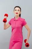 Kvinna för konditionflickapassform med hantlar som gör övning med dumma klockor som utbildar med vikter som isoleras på vit bakgr Fotografering för Bildbyråer