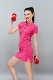 Kvinna för konditionflickapassform med hantlar som gör övning med dumma klockor som utbildar med vikter som isoleras på vit bakgr Royaltyfri Bild