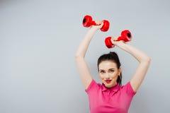 Kvinna för konditionflickapassform med hantlar som gör övning med dumma klockor som utbildar med vikter som isoleras på vit bakgr Royaltyfria Bilder