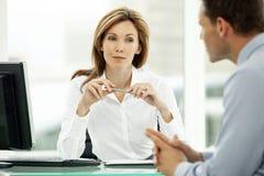 Kvinna för ledare för företags affär som i regeringsställning lyssnar till den unga affärsmannen royaltyfri foto