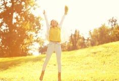 Kvinna för lyckligt uttryck för bladnedgång som ung har gyckel i varmt soligt fotografering för bildbyråer