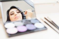 Kvinna för makeupkonstnär som gör smink genom att använda den kosmetiska borsten för dig Royaltyfri Foto