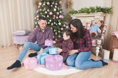 Kvinna för man för familjjulafton och liten unge med gåvor nära royaltyfri fotografi