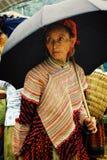 kvinna för medlem för stam för barnblommahmong på den lokala bondemarknaden som är hög upp i bergen med ett paraply royaltyfria bilder