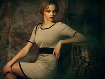 Kvinna för modemodell med idérikt sminksammanträde på en stol i dramagarnering arkivfoton