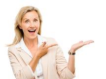 Kvinna för mogen affär som pekar tomt isolerat le för kopieringsutrymme royaltyfri bild