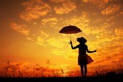 kvinna för paraply för hoppsilhouettesolnedgång arkivbilder