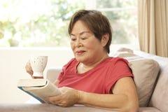 kvinna för pensionär för avläsning för bokdrinkutgångspunkt arkivbilder