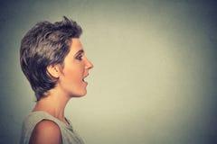 Kvinna för profil för sidosikt som talar med solitt komma ut ur hennes öppna mun arkivfoton