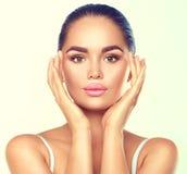 Kvinna för skönhetbrunettbrunnsort med perfekt makeup som trycker på hennes framsida arkivfoton