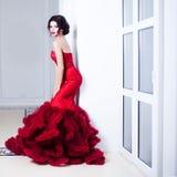 Kvinna för skönhetbrunettmodell i röd klänning för afton Makeup och frisyr för härligt mode lyxig Förförisk kontur En stan flicka royaltyfri foto