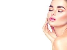 Kvinna för skönhetbrunnsortbrunett som trycker på hennes framsida Skincare Royaltyfri Foto