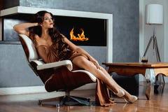 Kvinna för skönhetyong brunett som sitter nära spisen arkivbilder