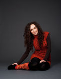 kvinna för smiley för lång pulover för golv sittande arkivbild