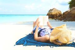Kvinna för sommarstrandferie som läser en bok på stranden i fri tid royaltyfri bild