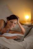 kvinna för sovrumaftonbärbar dator Arkivfoto