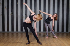 kvinna för sportar två isolerad white för kondition instruktör Kurs med en instruktör Två kvinnor som gör sträckning tillbaka som Royaltyfri Bild