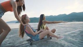 Kvinna för tre vänner som ler och rider på longboard på stranden på solnedgången lager videofilmer