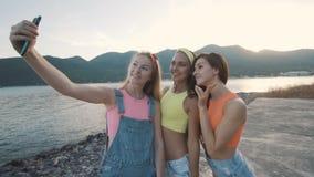 Kvinna för tre vänner som ler och tar självporträttfotoet med smartphonen arkivfilmer
