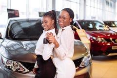 Kvinna för två afrikansk amerikan nära bilen med tangenter i handen - begrepp av köpandebilen royaltyfria bilder