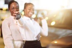Kvinna för två afrikansk amerikan nära bilen med tangenter i handen - begrepp av köpandebilen arkivfoto