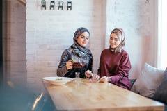 Kvinna för två caucasian muslim som dricker te i kafé royaltyfria bilder