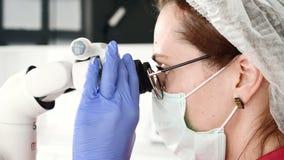 Kvinna f?r n?rbild A i exponeringsglas med en yrkesm?ssig tandl?kare som arbetar med ett yrkesm?ssigt stamotological mikroskop i  stock video