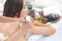 kvinna f?r vatten f?r brunnsort f?r h?lsa f?r huvuddelomsorgsfot Ung asiatisk kvinna som har massage med varma växt- bollar för d arkivfoton