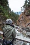 Kvinna från det tillbaka anseendet på en bro på den tyska vattenfallet - Kuhfluchtwasserfall - nära de tyska fjällängarna medan Fotografering för Bildbyråer