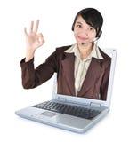 Kvinna för appellmitt med hörlurar med mikrofon som ler ut ur bärbara datorn Royaltyfri Foto