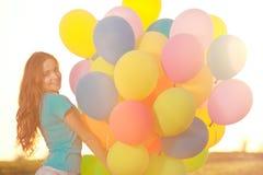 Kvinna för lycklig födelsedag mot himlen med regnbåge-färgade luftlodisar Arkivfoto