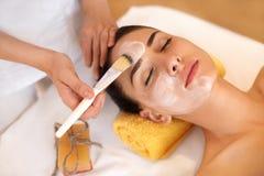 kvinna för white för behandling för gurkaframsidamaskering Kvinnan i skönhetsalong får Marine Mask Arkivbild