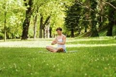 Kvinna för Zenyogaposition på gräset Arkivbilder