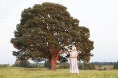 Kvinna framme av det stora trädet i parkeratappningstilen i det ensamma begreppet, grön jord för ensam natur Arkivfoto