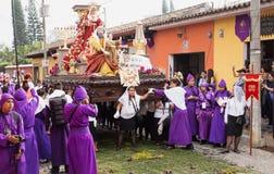 Kvinna framme av en flöte med Mary, John och Jesus överst på processionen av San Bartolome de Becerra, Antigua, Guatemala Arkivbilder
