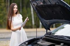 Kvinna framme av hennes brutna bil för bil Royaltyfri Bild