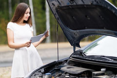 Kvinna framme av hennes brutna bil för bil Arkivfoton