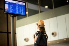 Kvinna framme av panelen för information om flygplatsflyg Arkivbilder